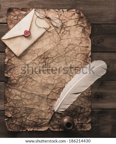 Writing accessories on a vintage paper on wooden background