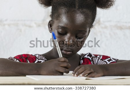 Writing Activity - Little beautiful African Girl In 1st grade. - stock photo