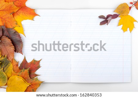 Writing-book and autumn leaves. Concept for Back to school