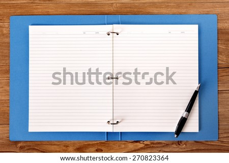 Writing book on student desk, ballpoint pen, copy space - stock photo