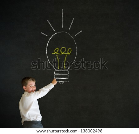 Writing boy dressed up as business man with bright idea chalk background lightbulb on blackboard background - stock photo
