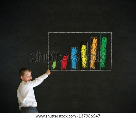 Writing boy dressed up as business man with chalk graph or chart on blackboard background