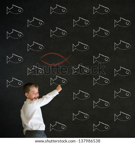 Writing boy dressed up as business man with independent thinking Jesus, God, Christianity fish on blackboard background - stock photo