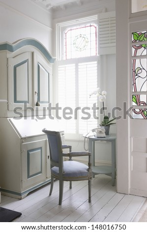 Writing bureau; chair and table by window at home - stock photo