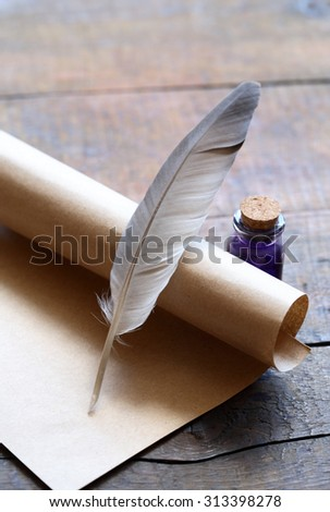 Writing concept. Closeup of scroll and quill near ink-pot on wooden table - stock photo