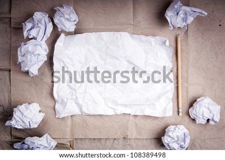 Writing concept - crumpled up paper wads with a sheet of white paper and pencil - stock photo