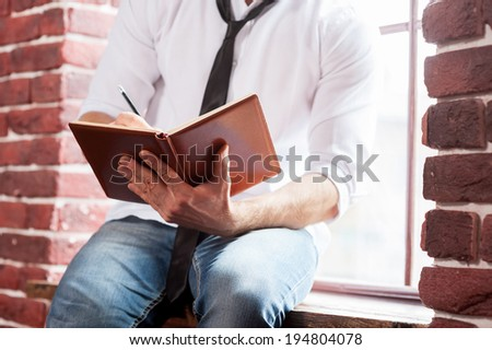 Writing down his thoughts. Close-up of young man in shirt and tie writing something in note pad while sitting at the window sill  - stock photo