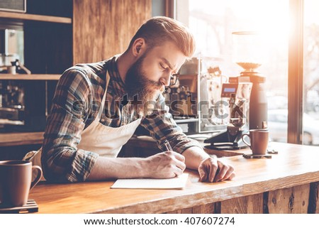 Writing down new coffee recipes. Young bearded man in apron writing in notebook while leaning to bar counter at cafe - stock photo
