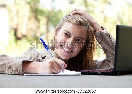 writing female student working on laptop outdoors