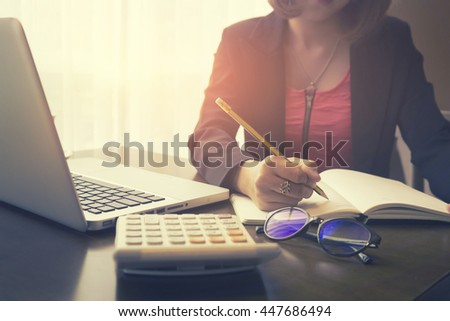 writing,female writes information from portable net-book while prepare for lectures in University campus,hipster woman working on laptop computer while sitting in cafe,vintage color,selective focus - stock photo