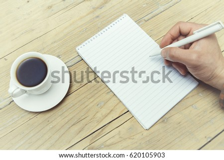 Writing hand and cup of coffee on wooden background (table)