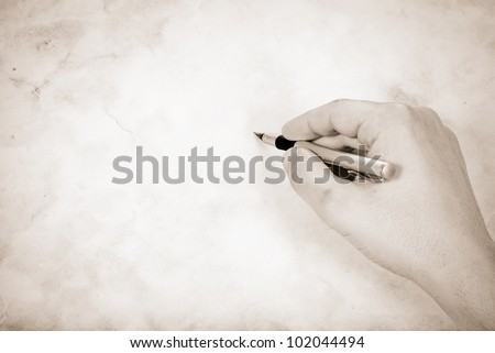 writing hand at old vintage paper parchment background - stock photo