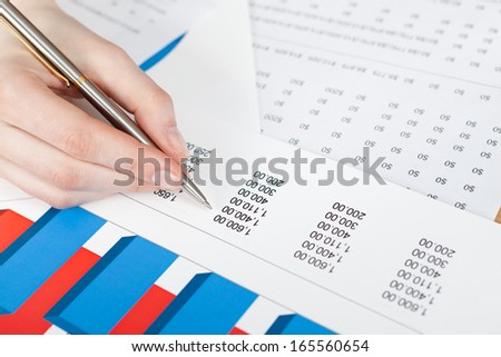 Writing hand. Business documents and graphs