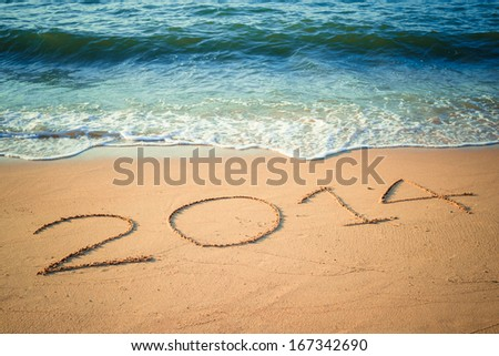 Writing Happy New Year's 2014 on the Beach in Thailand - stock photo