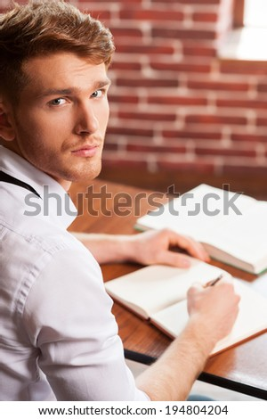 Writing his new roman. Top view of handsome young man in shirt and tie writing something in note pad and looking at camera while sitting at his working place  - stock photo