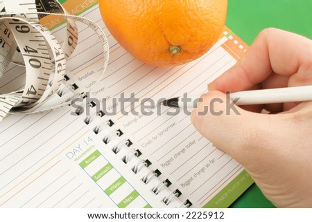 writing in a diet and nutrition journal with orange and tape measure to the side - stock photo