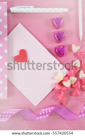 Writing love letters and cards for Happy Valentines Day with heart shape candy on pink shabby chic wood background - vertical, with applied retro faded filters.