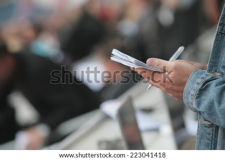 writing notebook reporter in a stadium - stock photo