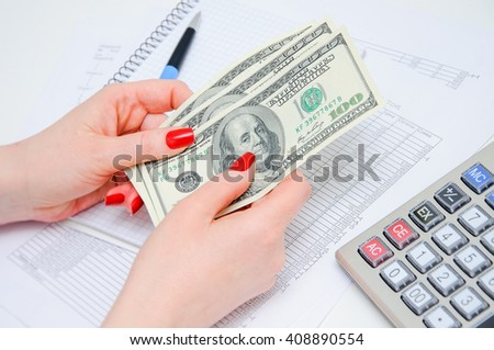 Writing of the report on work, leading of financial results. Calculation of the income. Woman hold money in hand. - stock photo