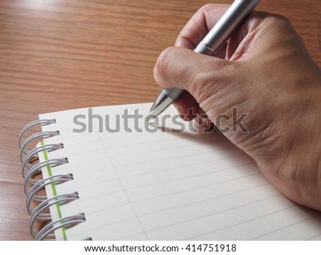 Writing on opened notebook with spiral on wood background
