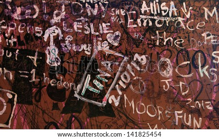 Writing on the Wall - Random words and phrases are scrawled across a wall of an old building. - stock photo