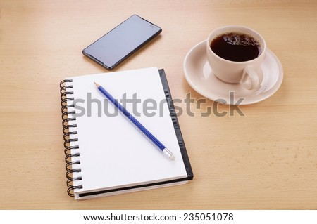 writing pad with pencil, smart phone and cup of coffee on desk - stock photo