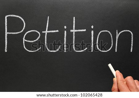 Writing Petition with white chalk on a blackboard. - stock photo