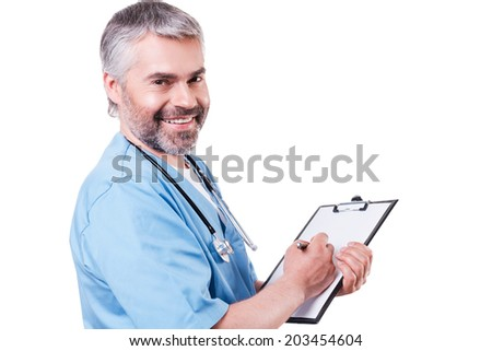 Writing RX prescription. Side view of mature doctor looking at camera and smiling while writing something at his clipboard and standing isolated on white - stock photo