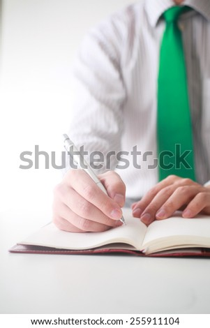 Writing something on a note pad - stock photo