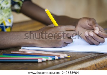 Writing Symbol - African Child Drawing on Paper in School Background - stock photo
