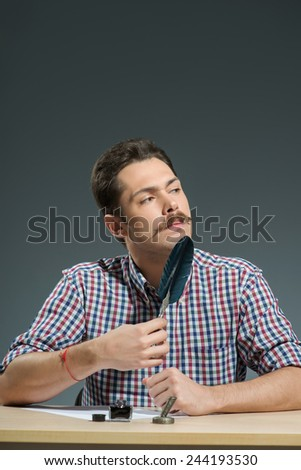 Writing with feather pen. Close-up of man writing with feather pen and inkbottle while sitting against grey background - stock photo