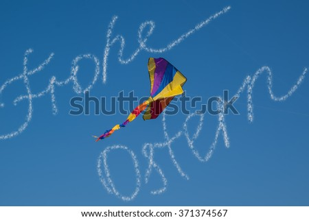 Written congratulation Happy Easter of the clouds on the bright blue sky in German. Air colorful kite soaring in the sky
