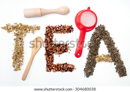 Written tea word with camomile, dog rose and green tea herbs. - stock photo
