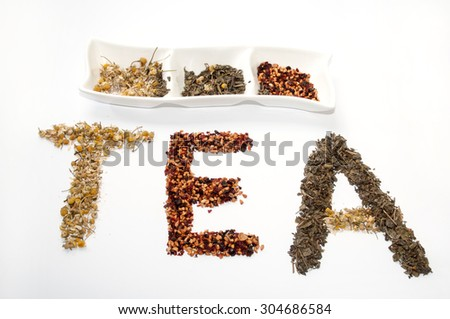 Written tea word with chamomile, dog rose and green tea herbs. - stock photo