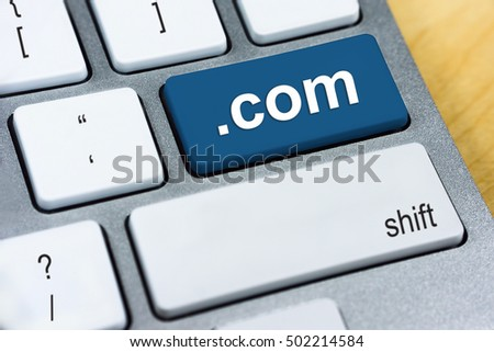 Written word .com abbreviation for Domain Name System of the Internet on blue keyboard button. Internet and Website Concept