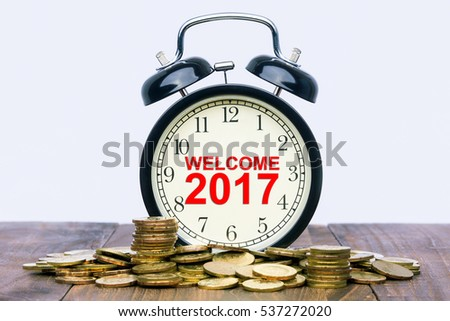 Written word Welcome 2017 on a clock with gold coins on top of a wooden table. Financial Wealth Concept.