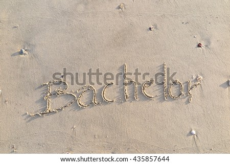 "written words ""Bachelor"" on sand of beach"