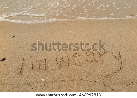 "written words ""I'm weary"" on sand of beach"