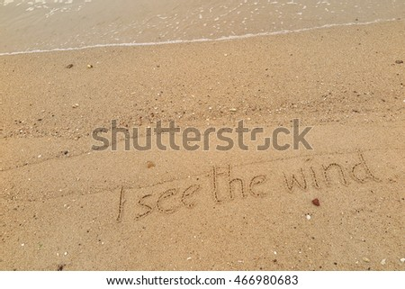 "written words ""I see the wind"" on top the wave sand of beach"