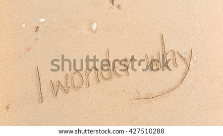 "written words ""I wonder why"" on sand of beach"