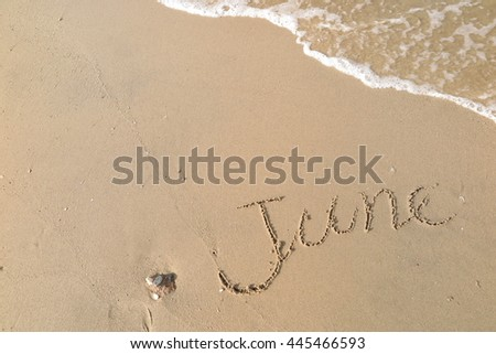 "written words ""June"" on sand of beach"