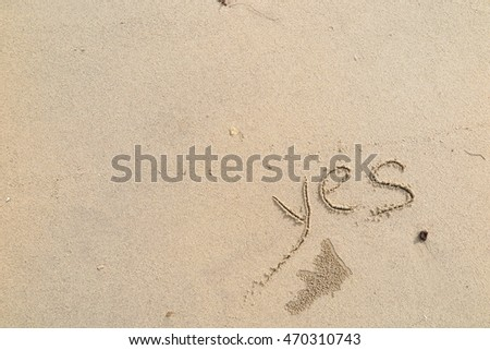 "written words ""yes"" on sand of beach"
