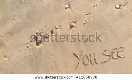 "written words ""you see"" on sand of beach"