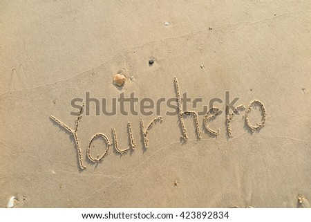 "written words ""Your hero"" on sand of beach"