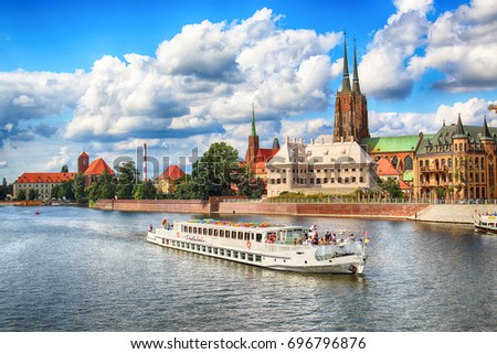 WROCLAW, POLAND - AUGUST 14, 2017: Wroclaw Old Town. Cathedral Island (Ostrow Tumski) is the oldest part of the city. Odra River, boats and historic buildings on a summer day.