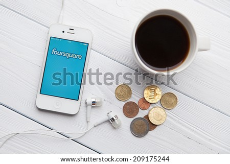 WROCLAW, POLAND - JULY 31, 2014: Photo of iPhone 4 smartphone device with Foursquare app running - stock photo
