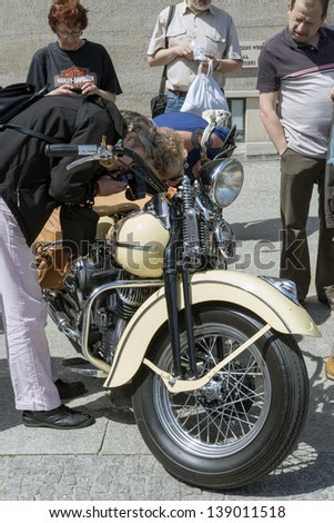 """WROCLAW, POLAND - MAY 18: People are watching Harley Davidson motorcycle parked in the city during """"Harley-Davidson Super Rally 2013"""" on May 18, 2013 in Wroclaw, Poland. - stock photo"""