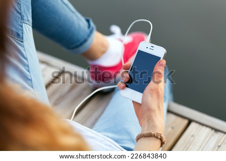 WROCLAW, POLAND - OCTOBER 12, 2014: Teenager sitting on a pier holding an Apple iPhone smartphone - stock photo
