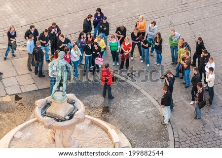 WROCLAW, POLAND - OCTOBER 7, 2009: Tourists with tourist guide gathered in front of Statue of Naked Fencer in front of University of Wroclaw. Statue was designed by Hugo Lederer and erected in 1904. - stock photo