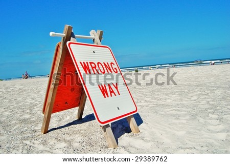 wrong way sign on a beach - stock photo